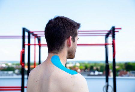 persona con nastro kinesiologico azzurro sulla spalla