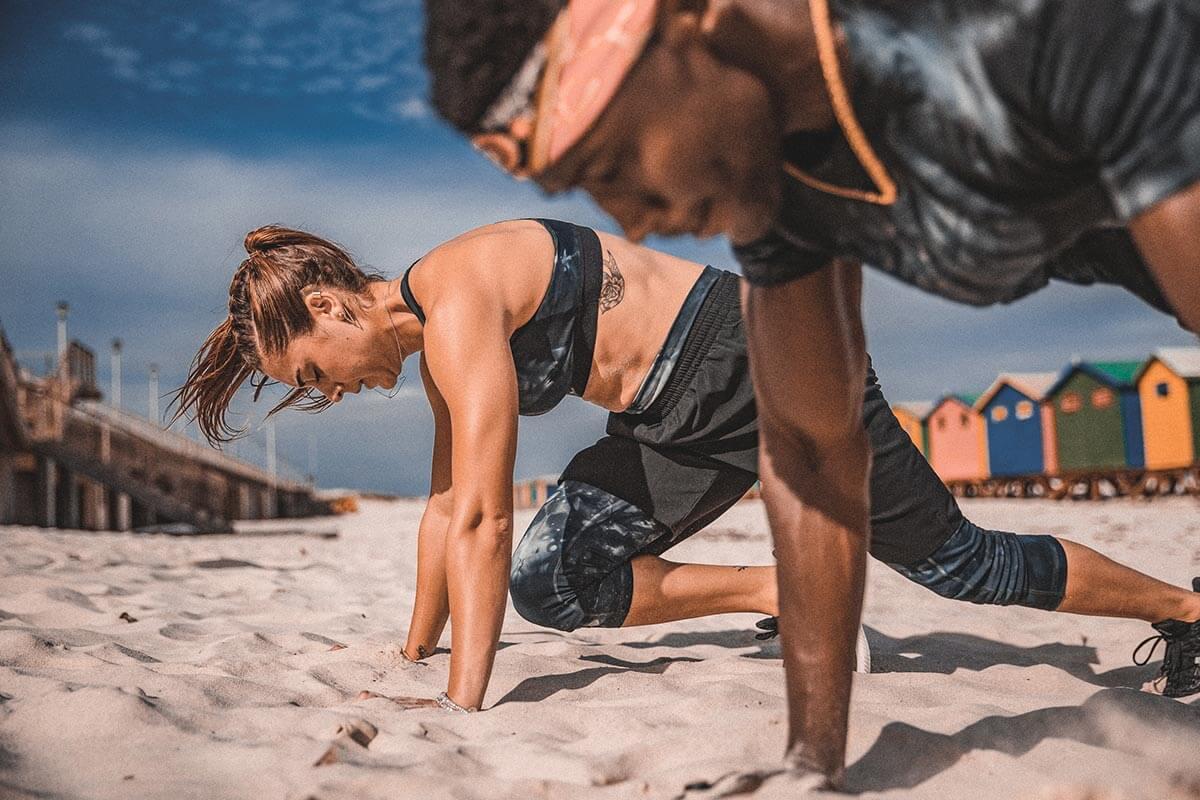 Homem e mulher praticando exercícios na praia
