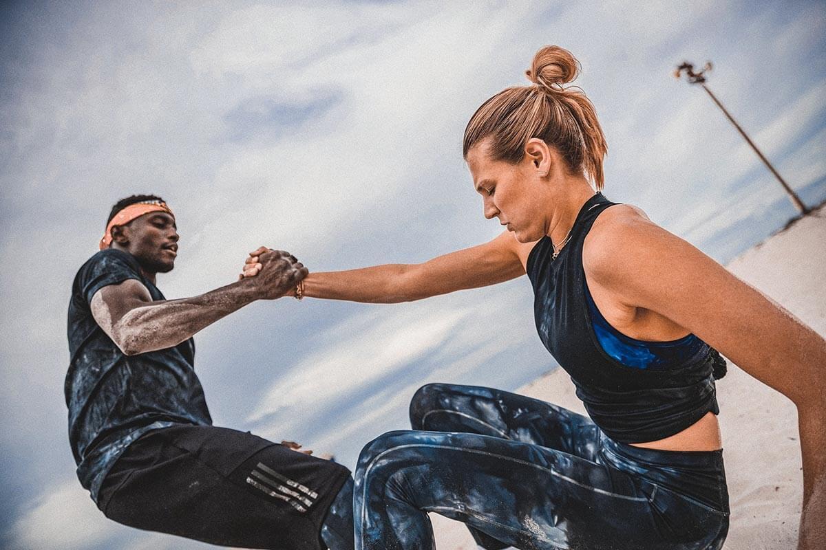 Mulher e homem fazendo exercícios em dupla na praia para aliviar o estresse
