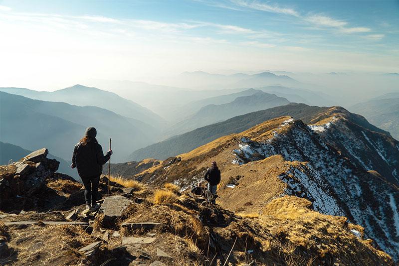 Un uomo e una donna camminano al sole in montagna