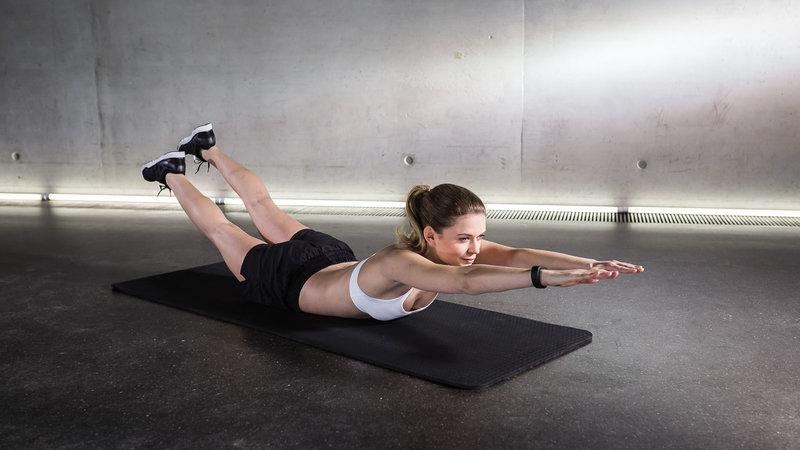 Atleta donna mentre svolge l'esercizio superman