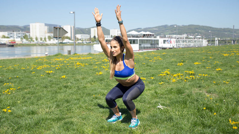 Young woman is doing Overhead Squats.