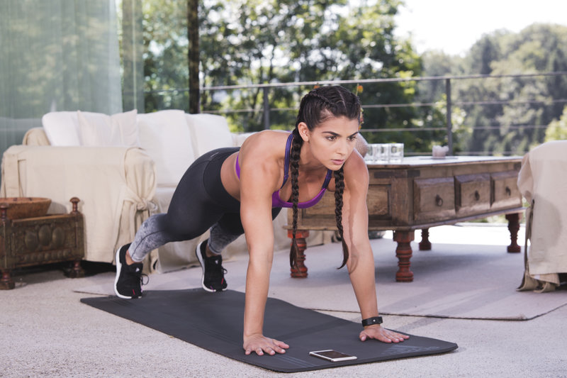 Fit woman doing a high plank at home.