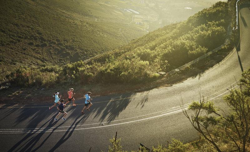 Groupe de coureurs sur une route entourée de verdure.