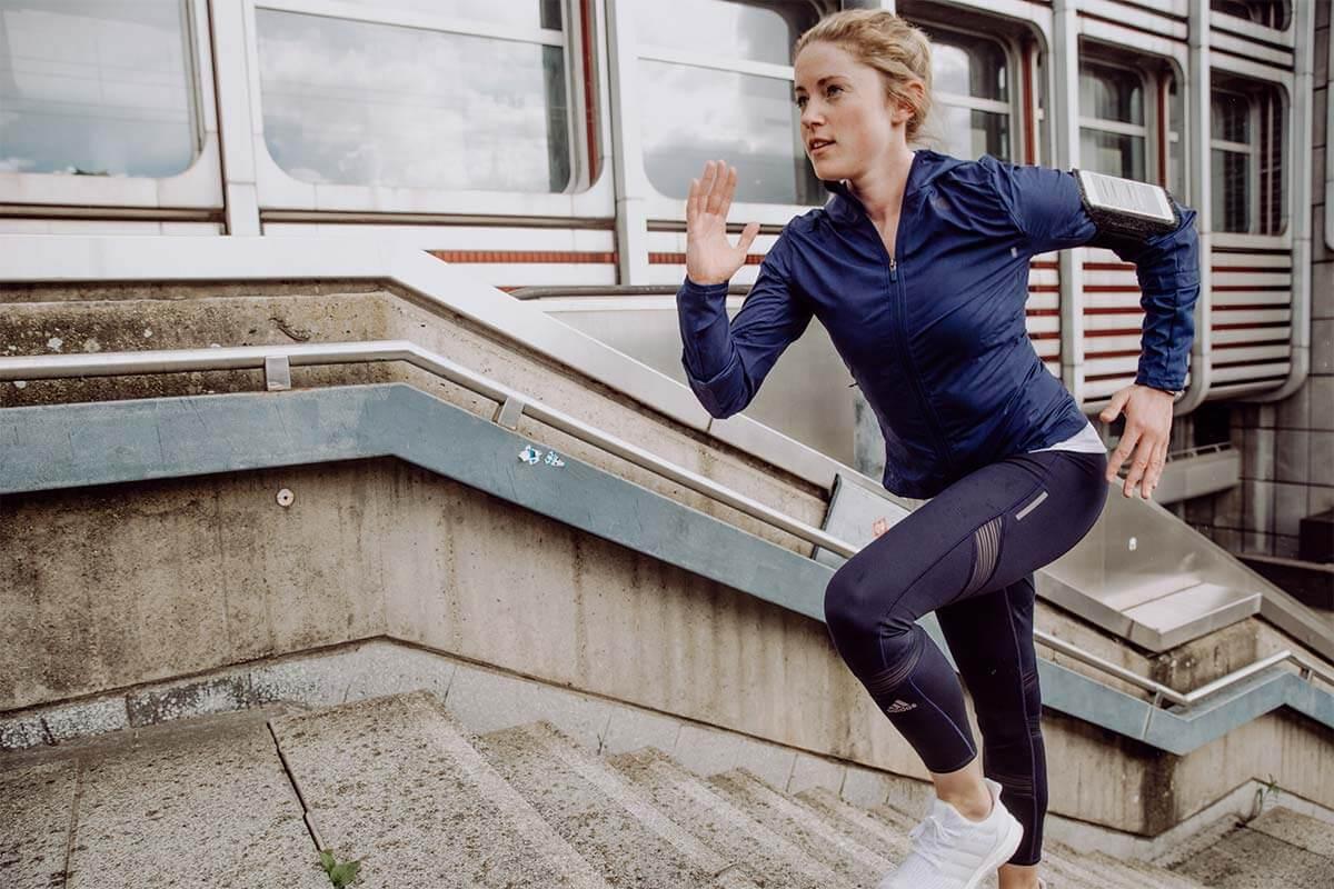 Mulher correndo enquanto sobe escadaria na rua