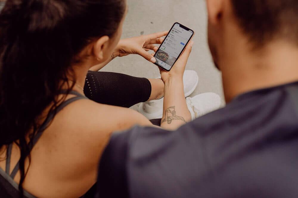 Mulher sentada ao lado de homem mexendo no celular