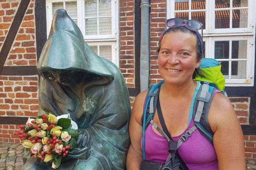 Hannah em sua cidade natal, ao lado de uma estátua