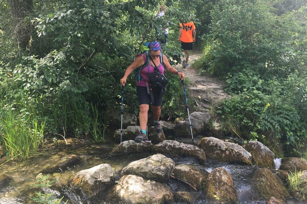 Hannah atravessnado um riacho com bastões de caminhada