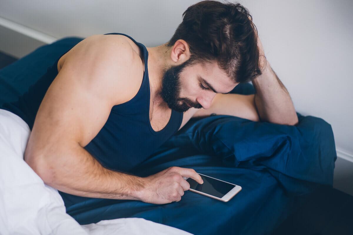 Homem deitado na cama, mexendo no celular