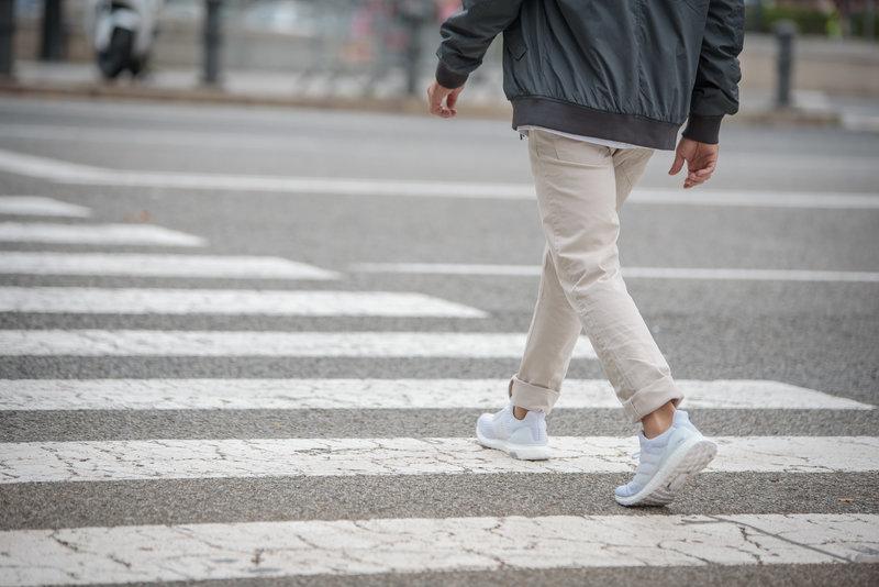 Ein Mann überquert auf dem Zebrastreifen die Straße