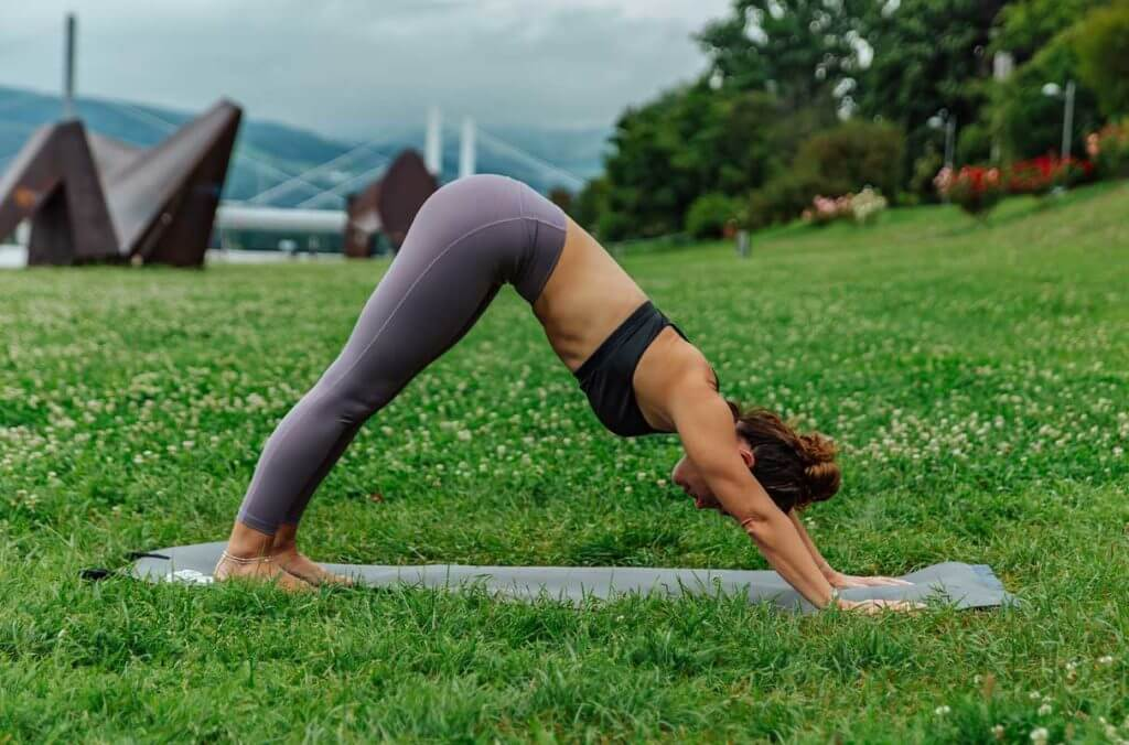 mulher praticando a postura de yoga cachorro olhando para baixo em um parque