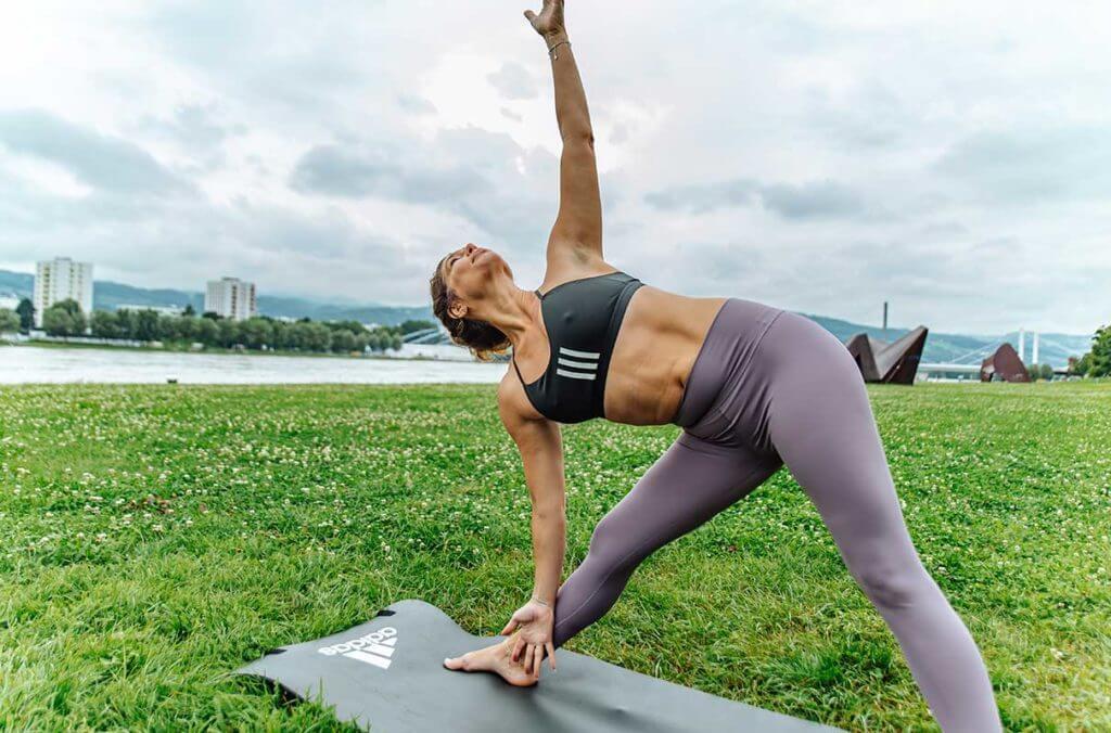 Mulher praticando yoga no parque para soltar a musculatura