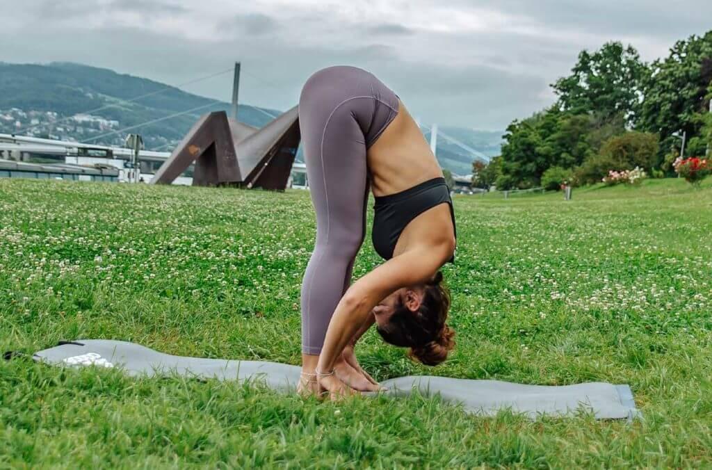 Mulher praticando uma flexão para a frente para alongar o corpo inteiro