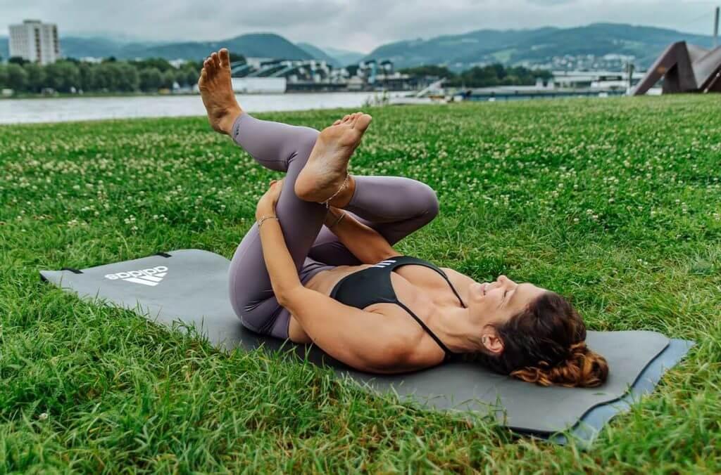 Mulher alongando os isquiossurais através de uma postura de yoga