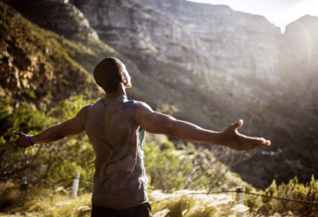 African athlete holding his arms out in the morning sun in appreciation for the natural beauty