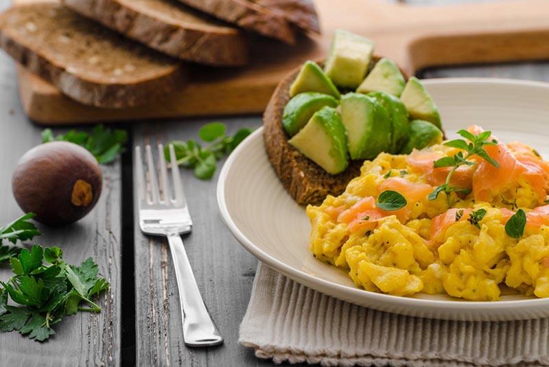 Nahaufnahme von einem Brot mit Avocado und Eierspeis mit Lachs.
