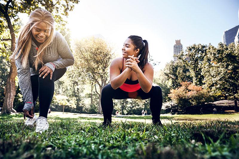 Zwei korpulente Frauen machen ein Workout im Park.