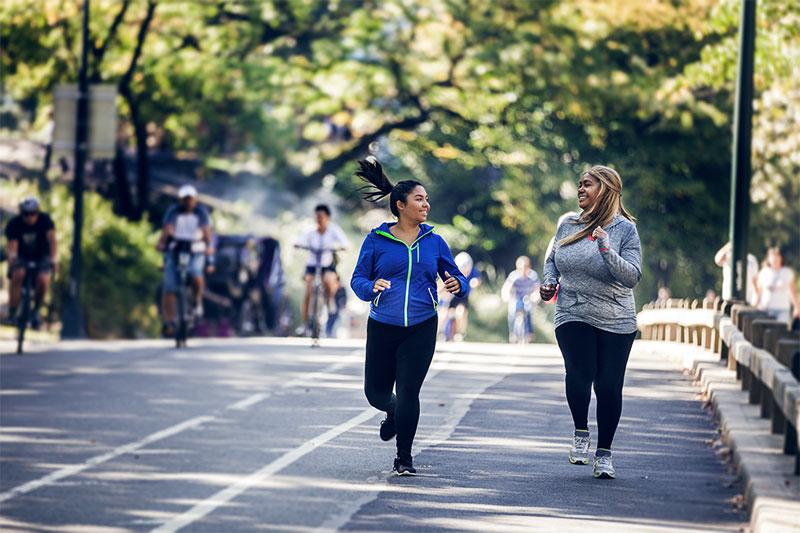 Zwei korpulente Frauen laufen im Park.