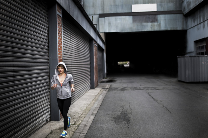 Woman running and listening to music next to a roller door in an urban street