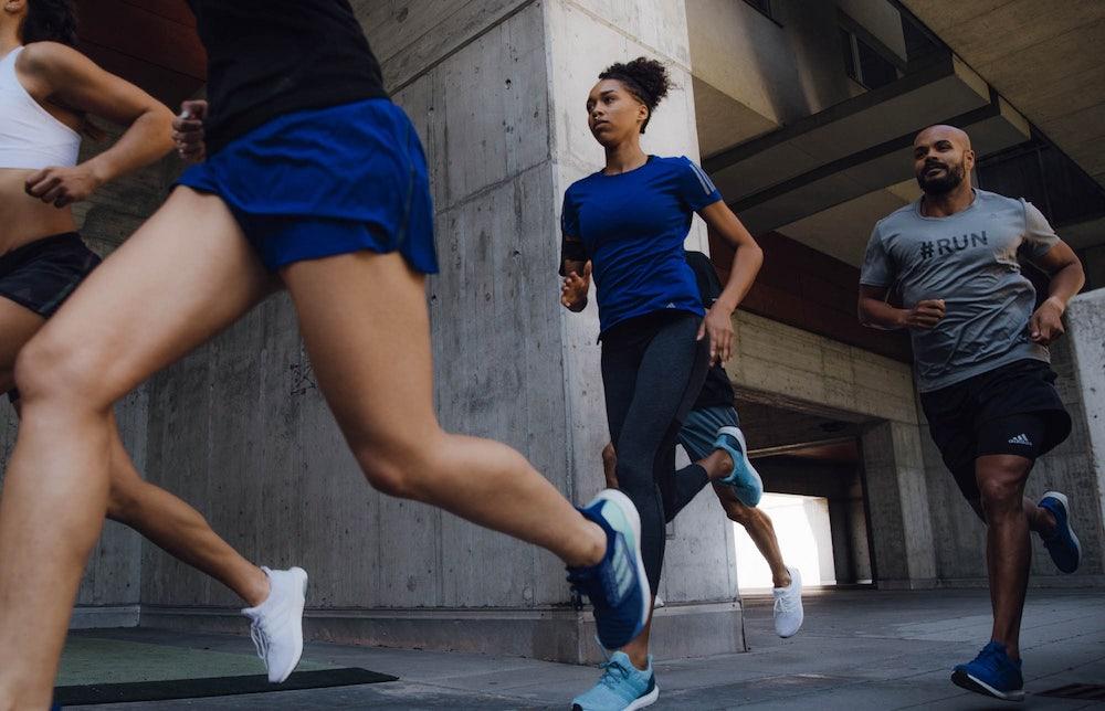 Eine Gruppe Läufer läuft in adidas-Kleidung durch eine Stadt