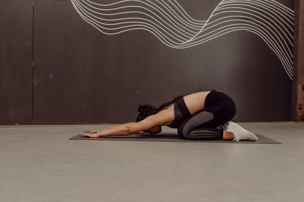 Eine junge Frau macht Yoga.