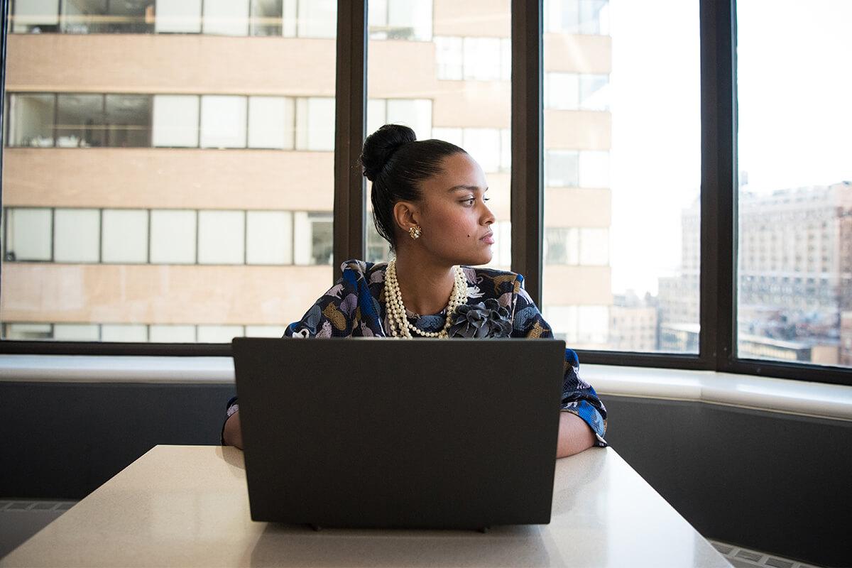 Eine junge Frau sitzt vor ihrem Laptop
