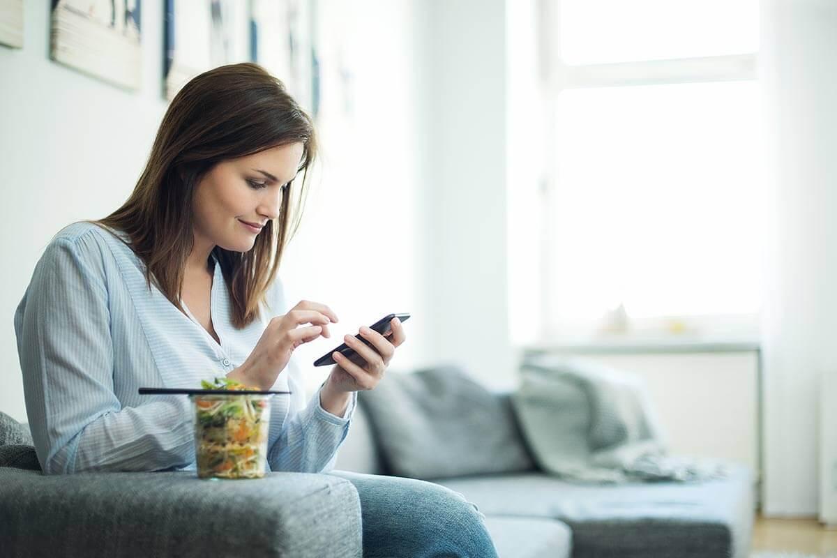 Donna guarda il telefono sul divano