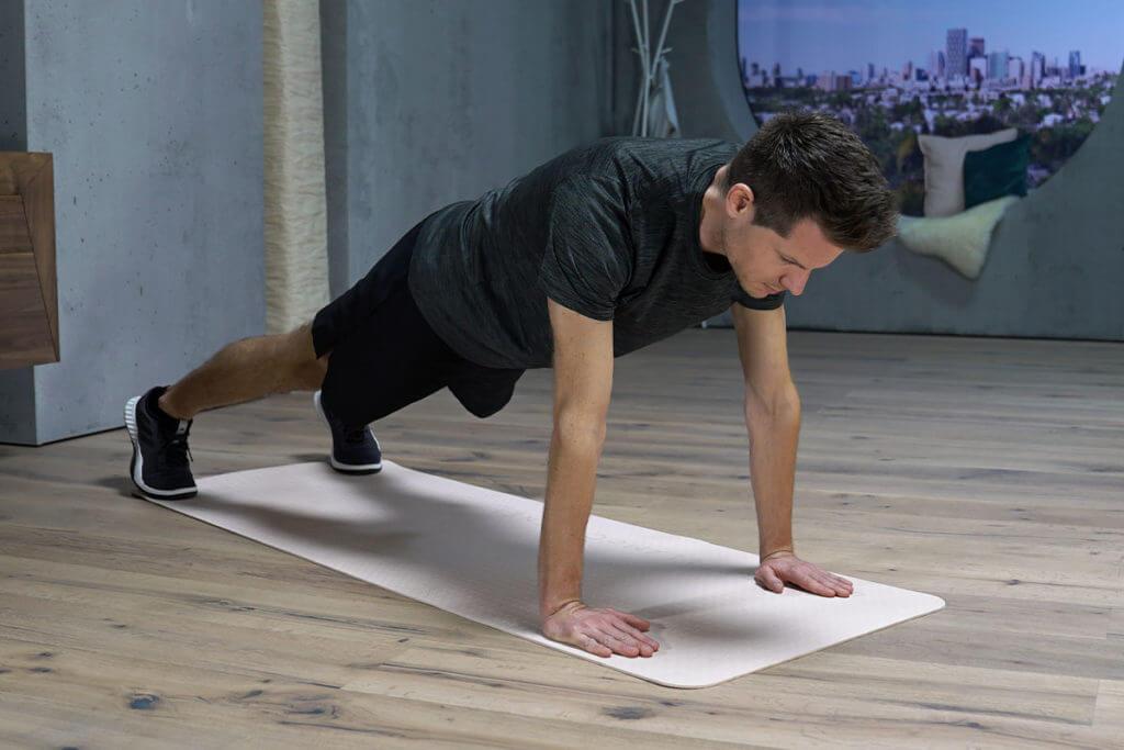Homem fazendo variação da prancha e de flexão para os braços