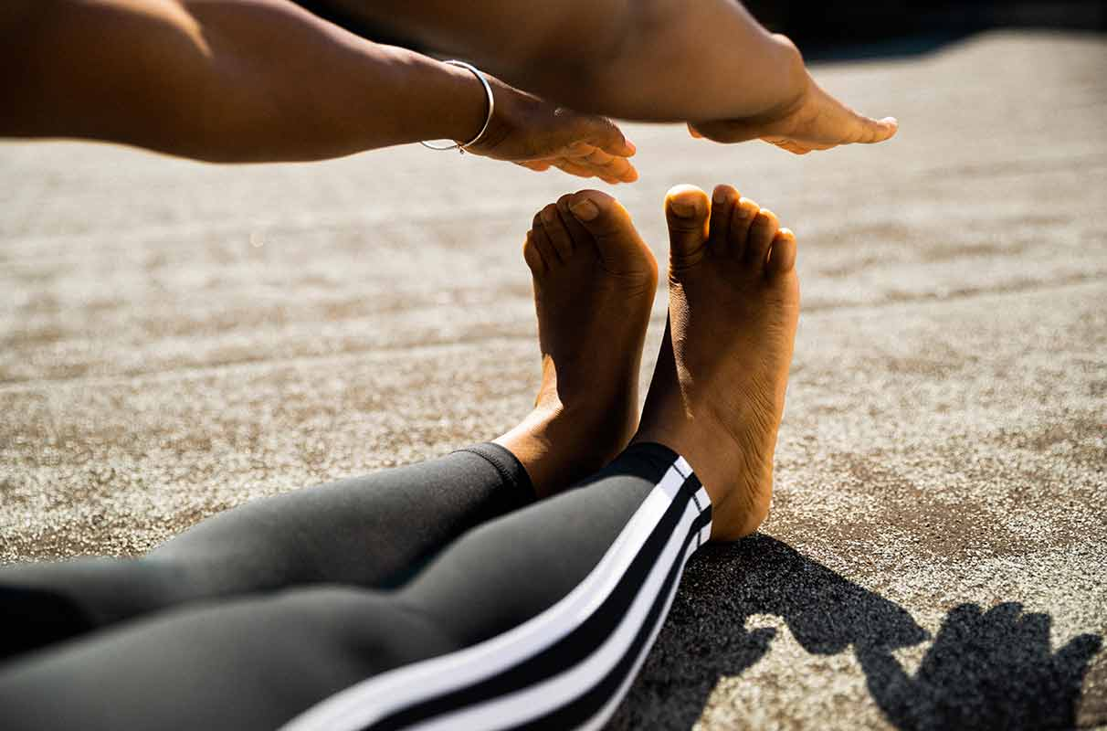 A young woman is doing some stretching after her workout