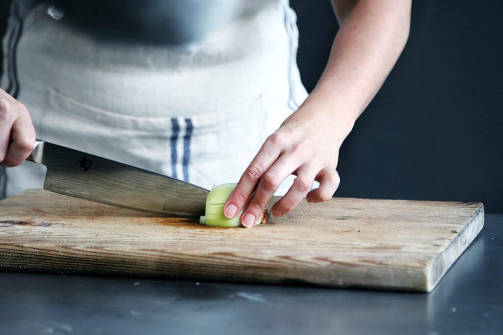 Mulher picando cebola, um alimento saudável da lista de compras