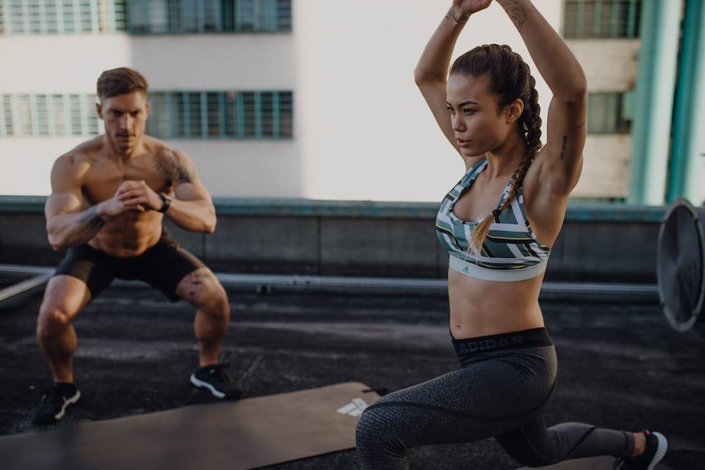 30-Day Squat Challenge: Zwei junge Menschen machen ein Beintraining am Dach eines Hochhauses