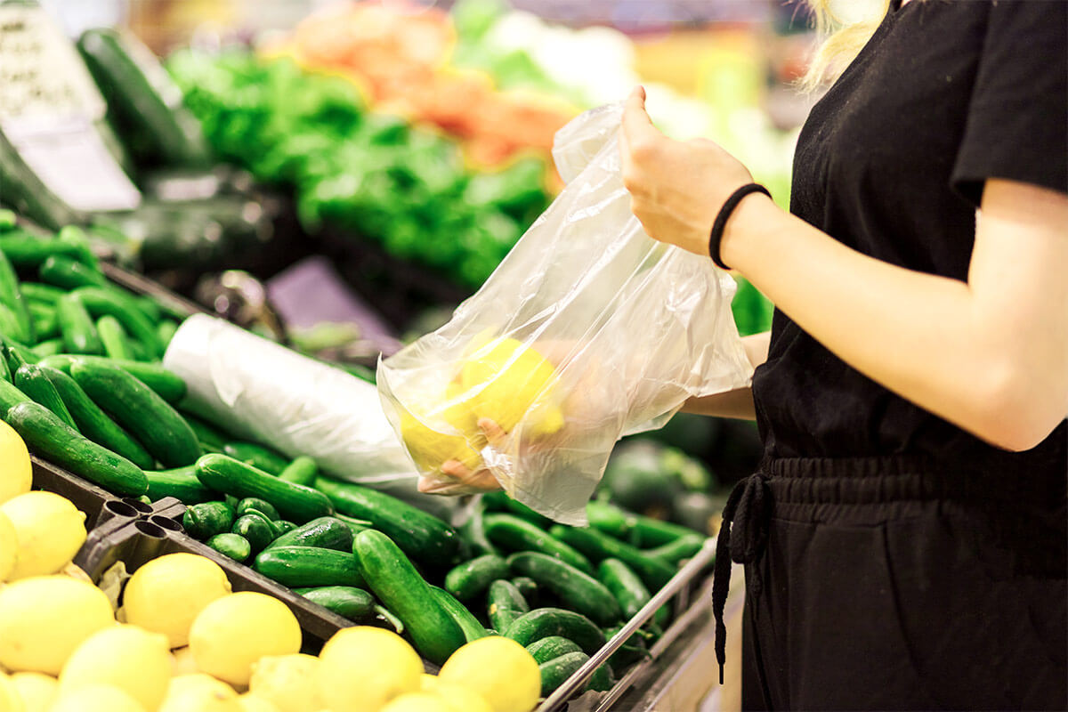 woman packing fruit in plastic bag
