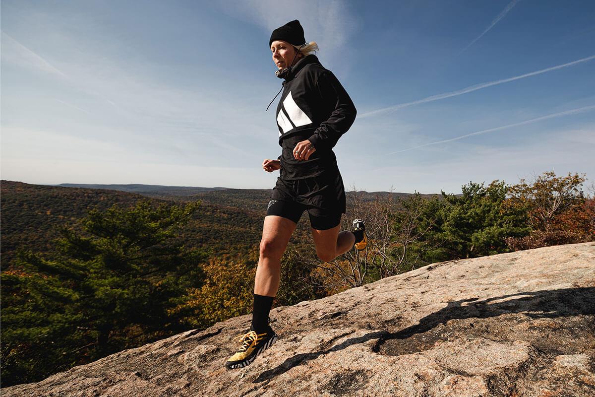 Mujer corriendo al aire libre por la montaña