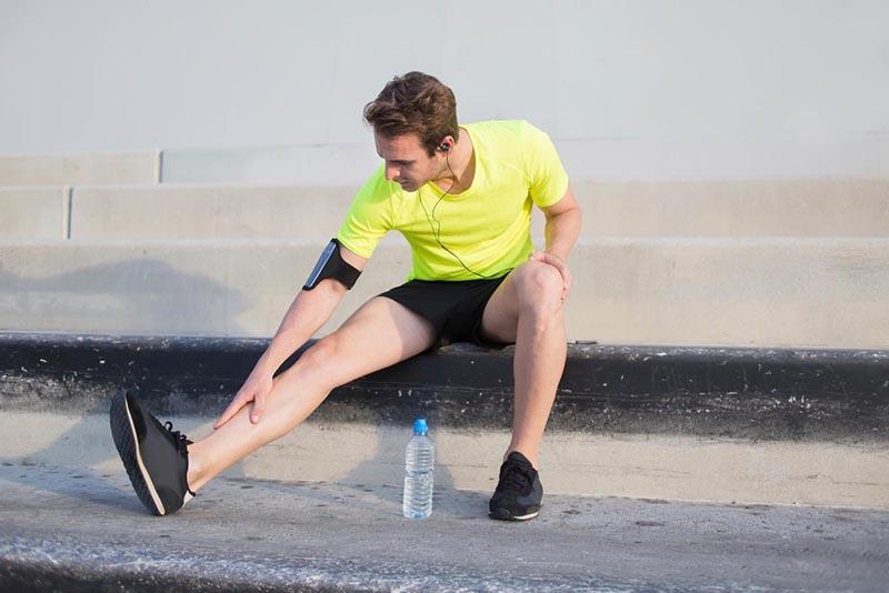 Ein Mann, der seine rechte Hand auf sein rechtes getrecktes Bein legt.