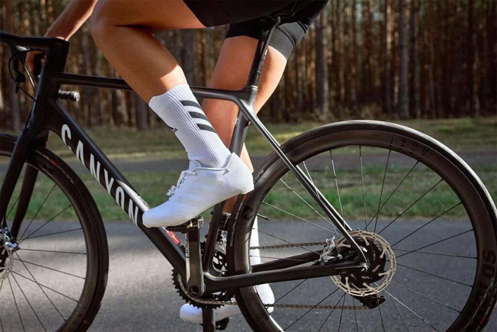Atleta praticando ciclismo em estrada cercada por uma floresta