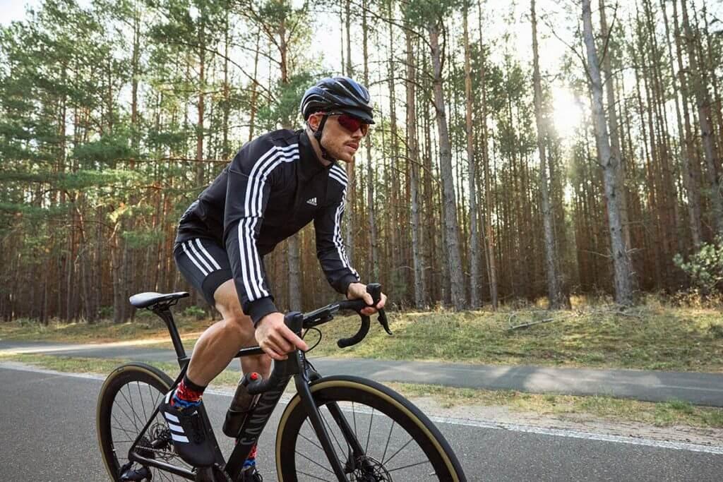 Atleta praticando ciclismo à beira da estrada, desfrutando da melhora no rendimento por treinamento de base