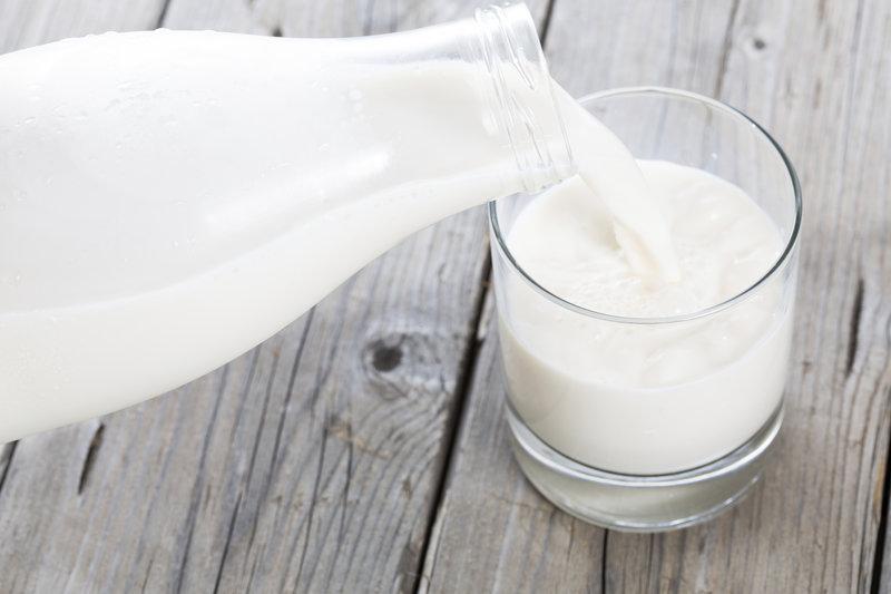 Vaso de leche llenándose de una botella