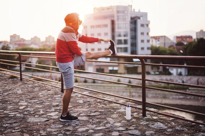 Junger Mann beim Dehnen seiner Beine an einem Gelaender.
