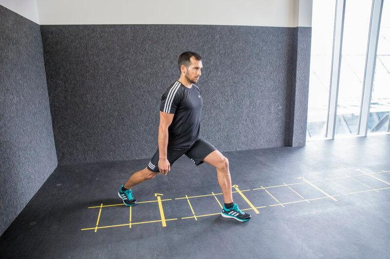 Athletischer Mann macht einen Ausfallschritt nach hinten mit Rumpfdrehung und Seitneigung.