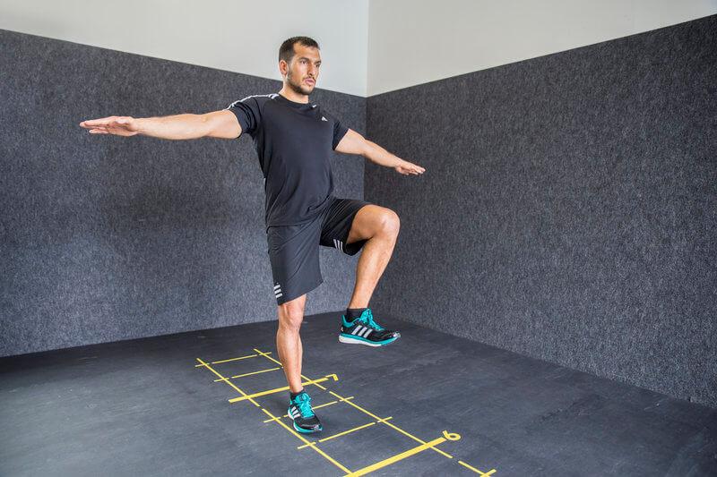 Athletischer Mann macht eine Standwaage mit folgendem Knie- und Fersenheben.
