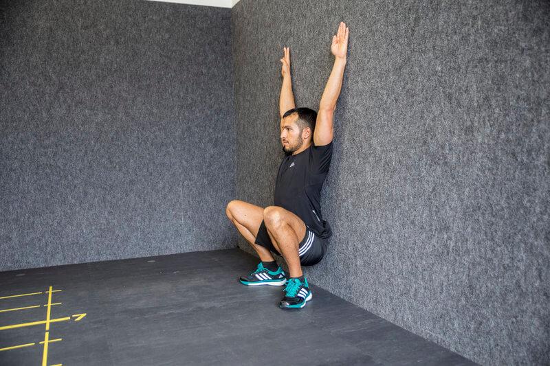 Junger Mann macht einen Wand-Squat.