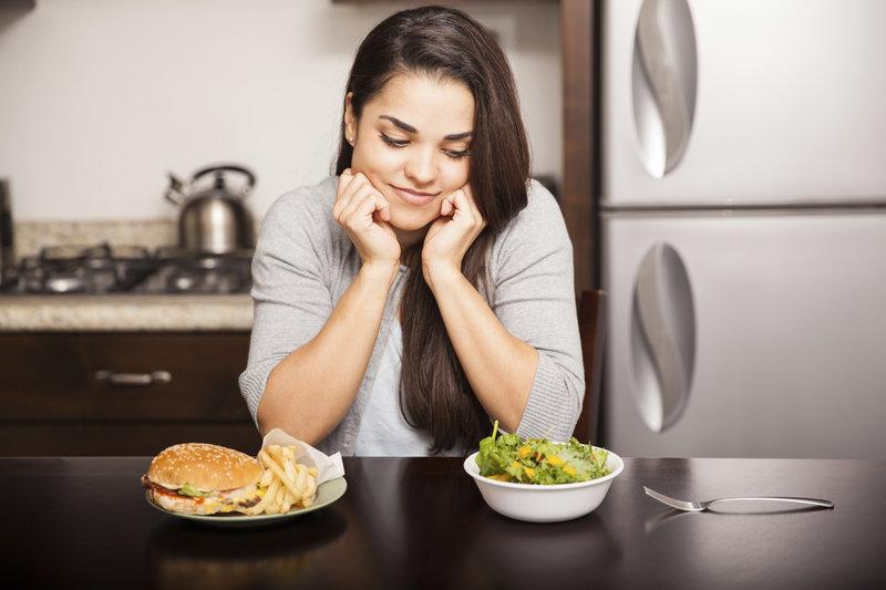 Frau versucht sich zwischen Burger und Salat zu entscheiden