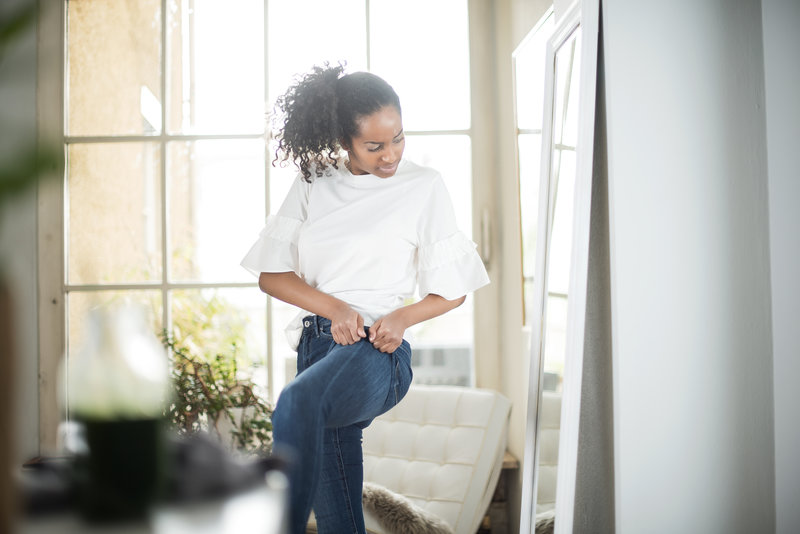 A woman trying to put in tight jeans in front of a mirror