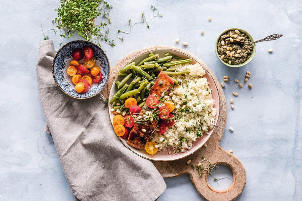 Salada saudável contendo quinoa, tomate, vagem e sementes