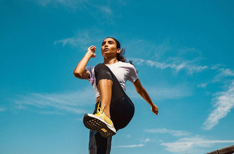Eine Frau in adidas-Sportkleidung macht Aufwärmübungen vor dem Laufen