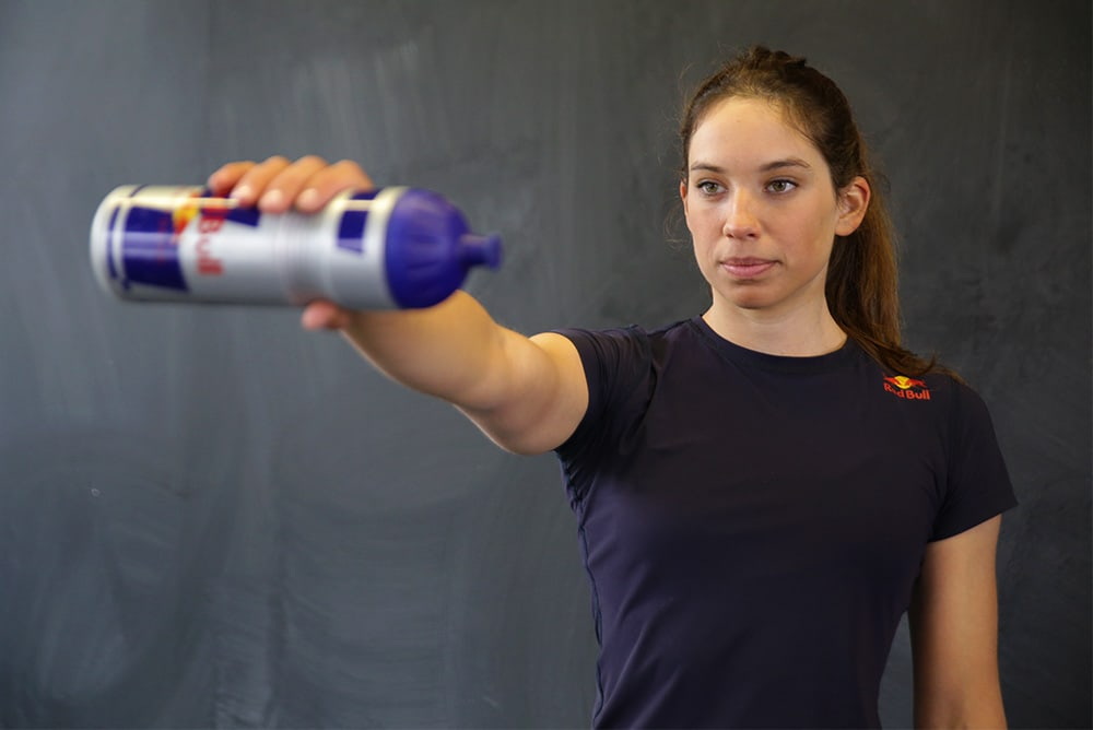 Frau macht Stabilisierungsübung mit einer Wasserflasche