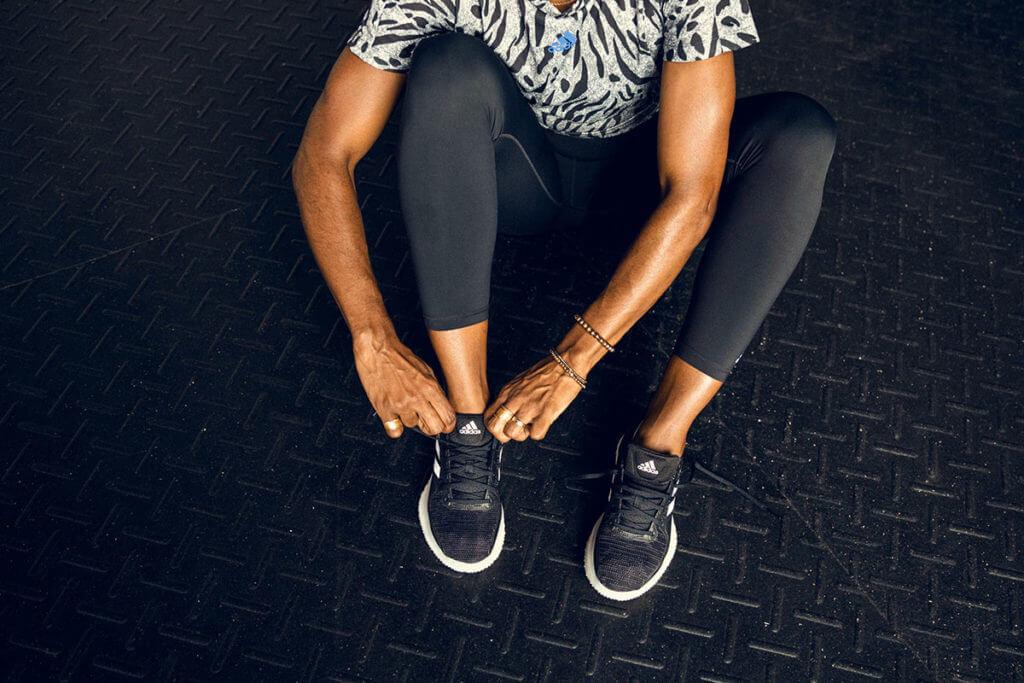 Eine Frau zieht sich ihre adidas Schuhe an
