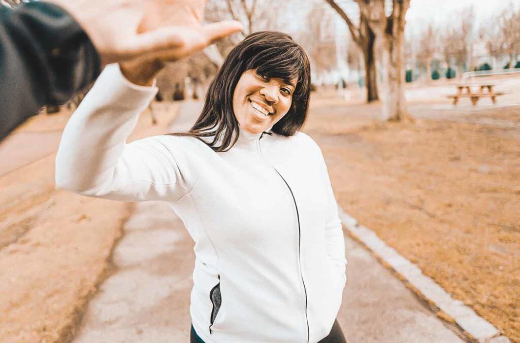 Mujer joven con una mentalidad de crecimiento sonriendo a la cámara muy motivada para entrenar