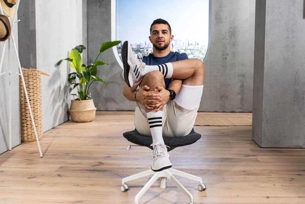 Homem praticando yoga sentado na cadeira para relaxar costas, ombros e pescoço