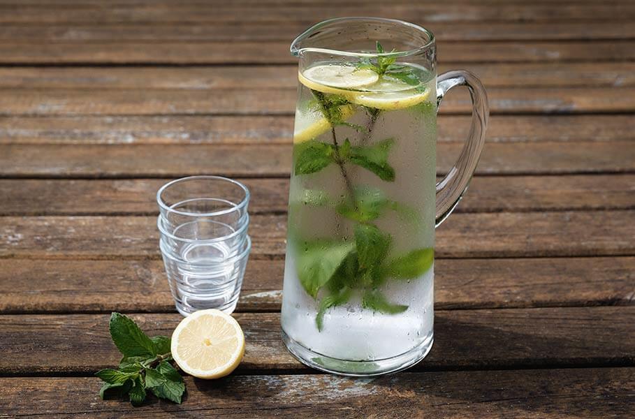 brocca d'acqua con foglie di menta e limone